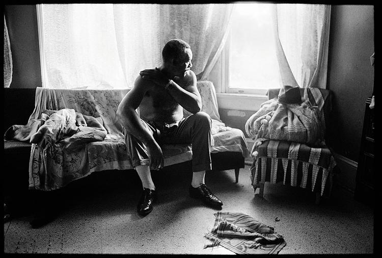 """Zdjęcie z albumu Tell It Like It Is, fot. David Alan Harvey""""James Liggins, głowa rodziny, siedzi na kanapie bez koszuli"""""""