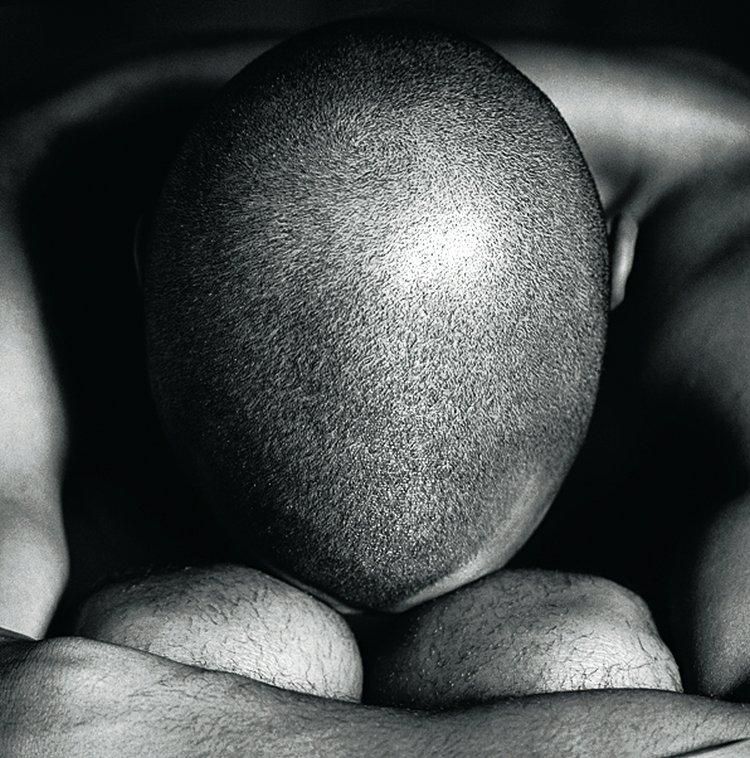 Zdjęcie zdaje się bardziej dosłowne, wyraźna tekstura tworzona przez włosy, symetrycznie ujęte kolana oraz ramiona tworzą zrównoważoną kompozycję. Ciemne, głębokie cienie wokół głowy modela nadają zdjęciu ponury nastrój (fot. John Freeman).