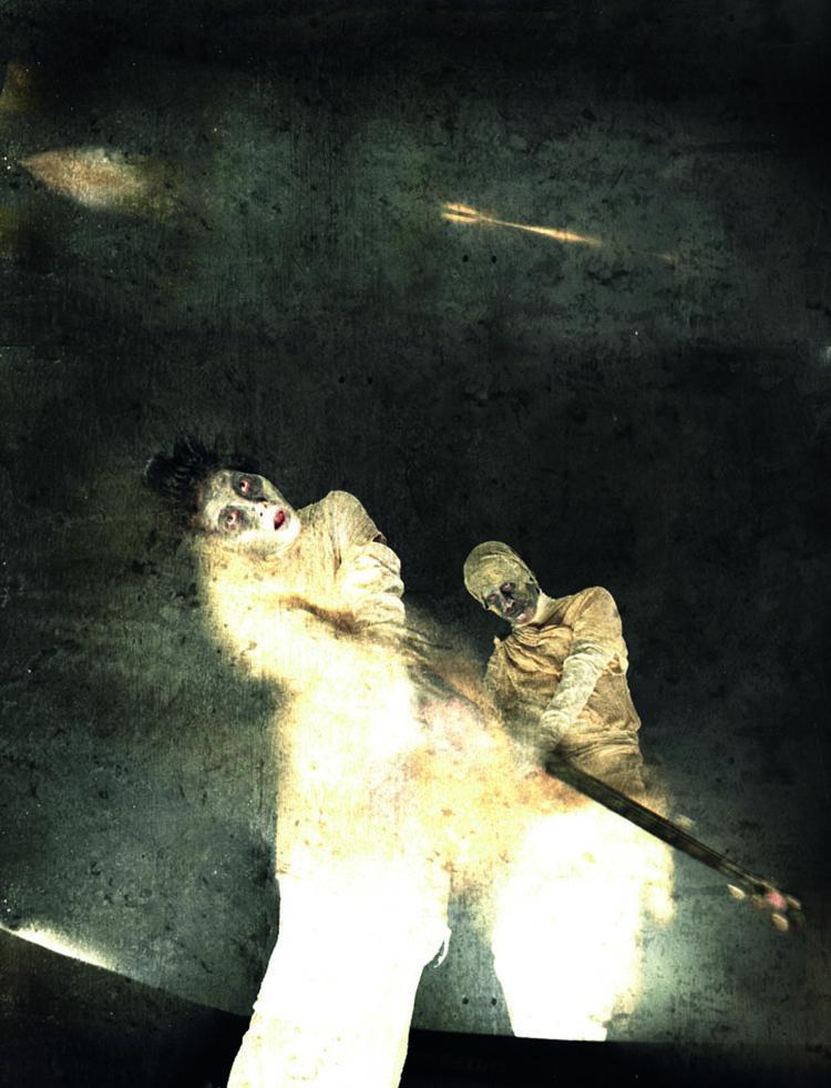 """The Cholmondeleys and Featherstonehaughs, 2008  """"Podczas przedstawienia, Tańcząc na twoim grobie chciałem uchwycić mroczny nastrój zombie. Złapałem zombie stojących na podium, oświetliłem od dołu i na tle czarnej kurtyny zrobiłem zdjęcie z bardzo niskiej perspektywy. Po lekkim rozmazaniu postaci w programie graficznym nałożyłem teksturę irozjaśniłem niektóre obszary"""" (fot. Chris Nash)."""