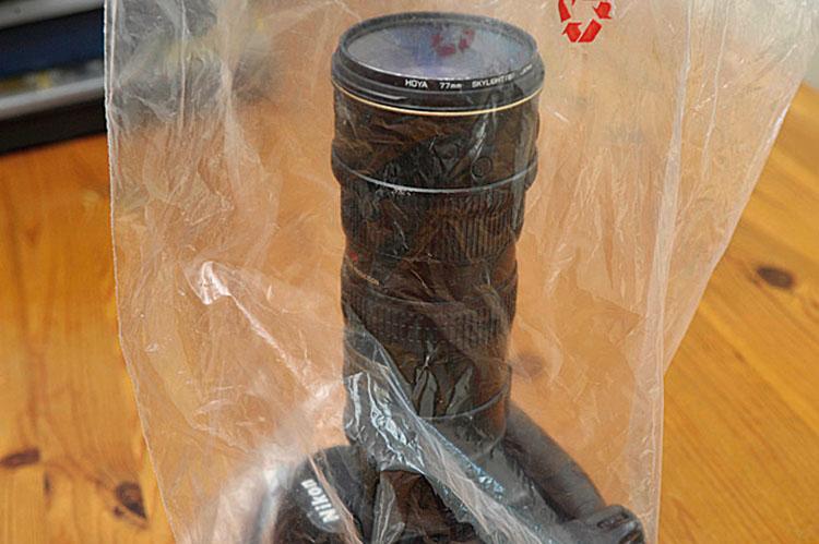 W torbie Znajdźcie czystą plastikową torbę, zdejmijcie osłonkę na obiektyw i załóżcie torbę na aparat i obiektyw, tak by jeden koniec torby dochodził do końca aparatu, adrugi obiektywu, upewnijcie się, że torba przykrywa cały aparat.