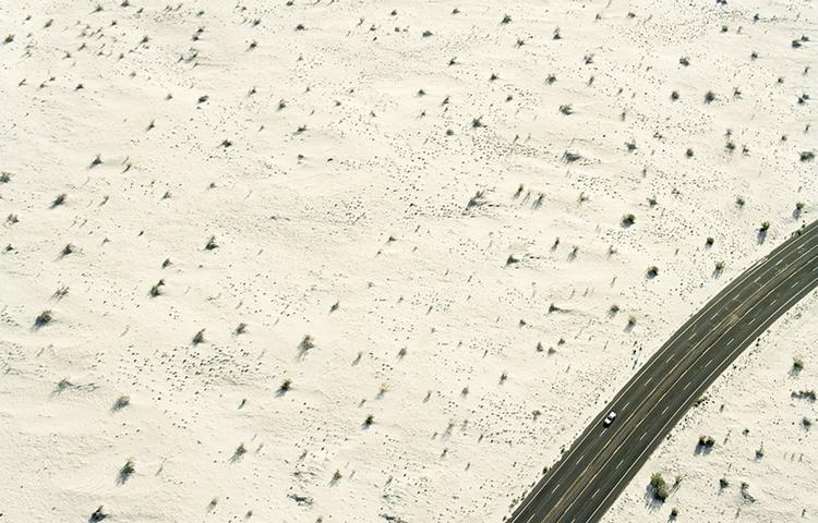Podróż przez pustynię Lecąc helikopterem nad pustynią, na południe od Los Angeles, fotograf zachwycił się rozciągającym się w dole krajobrazem. Poprosił więc pilota, aby zwolnił lot, by mógł wykonać kilka zdjęć. Pracował z kamerą filmową Mamiya Universal i, aby wibracje wywoływane przez helikopter nie wpływały negatywnie na ostrość obrazu, musiał użyć żyroskopu. Udało mu się zarejestrować, widoczne na zdjęciu w prawym dolnym rogu, drogę i samochód, dzięki czemu fotografia pustyni oddaje wrażenie skali.