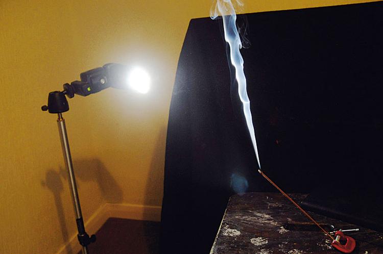 Oświetl dymBy podkreślić szczegóły, ustawiliśmy za naszym obiektem czarne tło. Następnie ze zrolowanego czarnego kartonu zrobiliśmy małą strumienicę na lampę, resztę papieru wykorzystaliśmy do wysłonienia tła i obiektywu, by nie sięgało tam światło błysku.