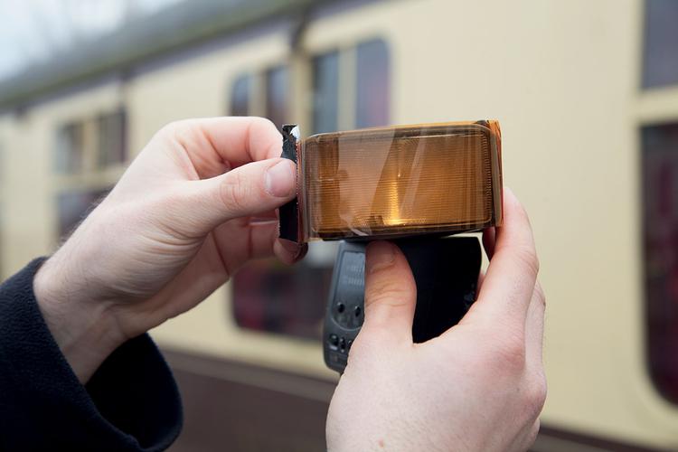 Zamocuj na fleszu filtr ocieplający i ustaw małą wartość zoomu lampy (35 mm zapewni odpowiednio szeroki strumień światła), po czym umieść ją w odległości ok. 1,8 m. Ja ustawiłem statyw na zewnątrz i skierowałem głowicę w stronę okna. Nie używaj nasadki zmiękczającej światło, aby stworzyć ostre cienie podkreślające opary mgły.