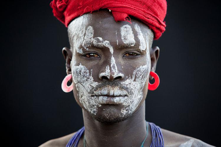 """Plemię Mursi, Dolina Omo, Etiopia, listopad 2014 """"Wyzwaniem przy fotografowaniu na tle dużej, czarnej zasłony uszytej w pracowni krawieckiej w Jinka było uzyskanie odpowiednio dużego obszaru czerni w kadrze, jak również zrównoważenie jasności tematu i tła"""", fot. Martin Middlebrook."""