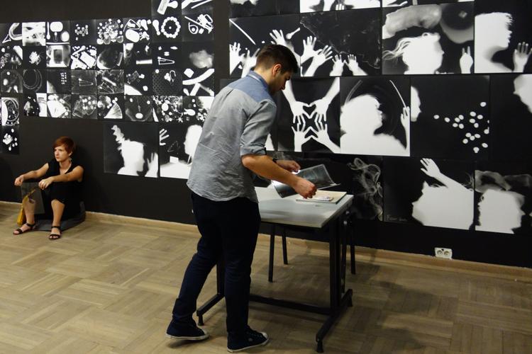 """Wszystkie prace, które powstają w przestrzeni warsztatowej są eksponowane na ścianach galerii Bunkier Sztuki. Na ścianach widzimy fotogramy, zrobione w ciemni naprzeciwko, przez osoby odwiedzające wystawę. Wystawa """"Oddźwięki"""" Jakuba Woynarowskiego, Miesiąc Fotografii w Krakowie 2014"""