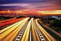 Uchwyć na zdjęciu kolorowe smugi świateł przejeżdżających samochodów