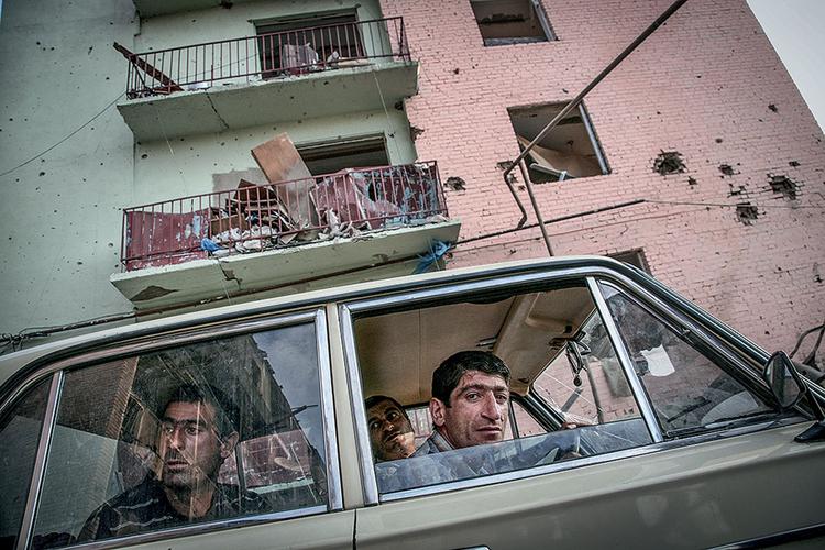 Mieszkańcy Gori przyglądają się zbombardowanym budynkom mieszkalnym. Gori, 2008 r. Fot. Justyna Mielnikiewicz