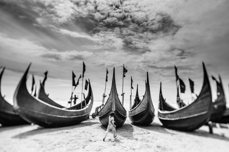 W wiosce Shamlapur nad brzegiem Zatoki Bengalskiej mieszka kilka tysięcy uchodźców. Niektórzy z nich od niedawna, część nawet od 20-30 lat żyje w Bangladeszu. Zasymilowani z lokalną społecznością Bengalczyków, wykonują pracę rybaków dla miejscowych biznesmenów. Na zdjęciu dzieci bawią się przy łodziach rybackich. Shamlapur (Bangladesz), październik 2013, fot. Marcin Zaborowski