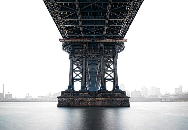 """Strażnik""""Chciałem sfotografować Nowy Jork z innej perspektywy. Ustawienie się z aparatem z szerokokątnym obiektywem bezpośrednio pod mostem pozwoliło mi uzyskać niecodzienną perspektywę i rzadko spotykaną głębię. Aby skupić uwagę oglądających na moście, zdecydowałem się prześwietlić panoramę miasta widoczną w tle"""""""