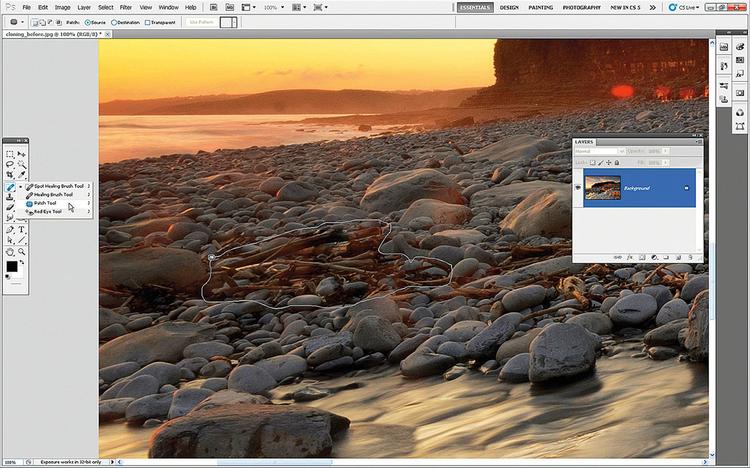 Właściwości narzędzia ŁatkaOtwórz plik klonowanie_przed.jpeg w Photoshopie CS5 lub 6. Aby usunąć sporą stertę drewna, znajdującą się po lewej stronie kadru, w inny sposób niż klonowanie, w palecie narzędziowej kliknij i rozwiń narzędzie Punktowy pędzel korygujący i wybierz narzędzie Łatka. Zaznacz opcję Źródło i obrysuj stos drewna.