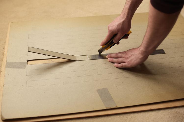 Aby zrobić maskownicę, potrzebujesz dużego arkusza kartonu. Wymierz i narysuj na nim długie prostokąty o wysokości 2,5 cm i długości 60 cm oddalone od siebie o ok. 2,5 cm. Następnie weź skalpel lub nożyczki i powycinaj prostokątne otwory. Użyj stalowej linijki, aby otrzymać proste krawędzie.
